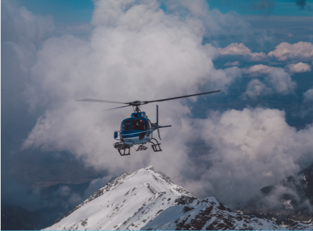 a helicopter over a snowy mountain top with clouds in the background